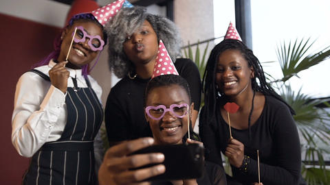 Portrait shot of four african girls making selfie on the smart phone Live Action