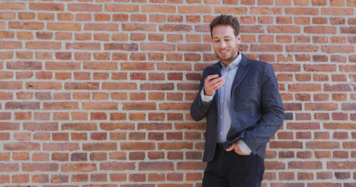 Man Using Phone - Smiling Businessman Using Smartphone Against Brick Wall Footage