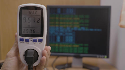 Closeup of power meter tool held by a young technician showing consumption Live Action