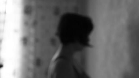 Silhouette of a lonely woman in depression in the room. Black and white Footage