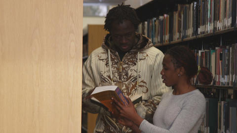 Shot of people in-between bookshelves at a library Footage