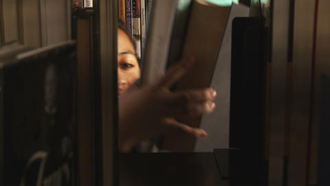 Girl pulling a book from a shelf in a library Footage