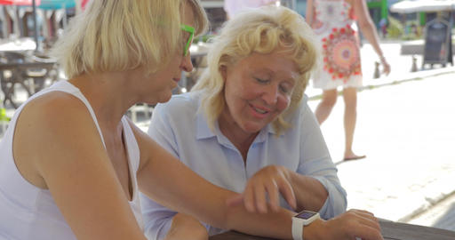 Senior women in street cafe using smart watch Footage