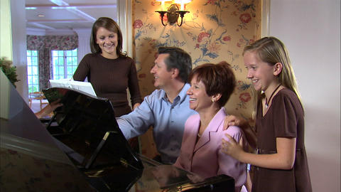 Family singing a song around a piano Live Action