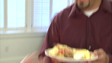 Cook handing a plate of hot food to someone Footage