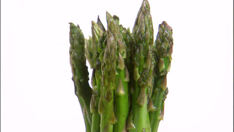 Zoom in on a bundle of asparagus rotating on a white screen Live Action