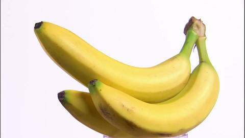 Bananas rotating on a white screen Footage