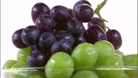 Close shot of grapes in a vase rotating on a white screen Footage