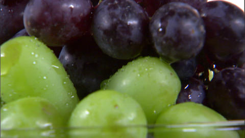 Tilt down shot of an assortment of fruit in a vase on a white screen Footage