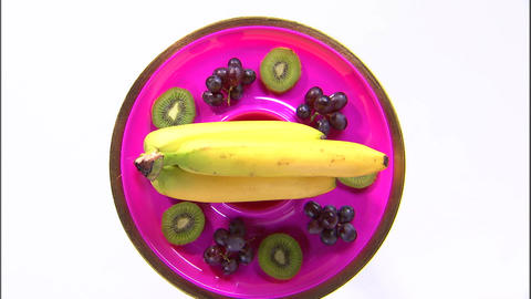 Assortment of fruit on a rotating purple plate Live Action