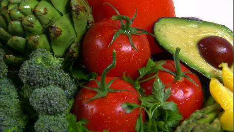 Close shot of an assortment of vegetables rotating on a white screen Footage