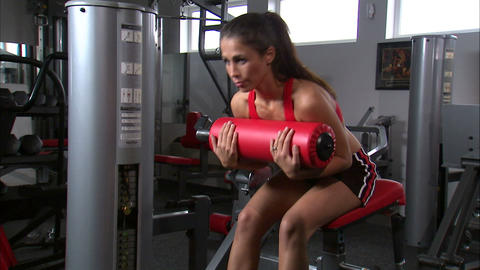 Woman doing curls on an exercise machine Footage