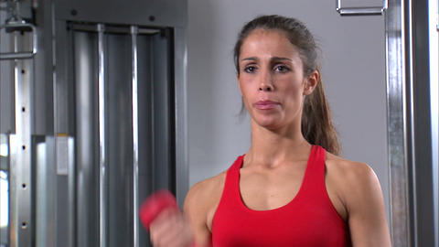 Woman doing arm curls with a pair of dumbbells in a gym Footage