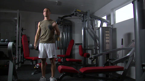 Man doing arm curls with a pair of dumbbells in a weight room Footage