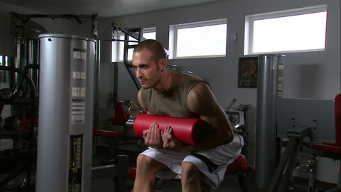 Man doing sitting curls with an exercise machine in a gym Footage