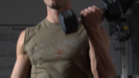 Man doing arm curls with dumbbells in a gym Footage
