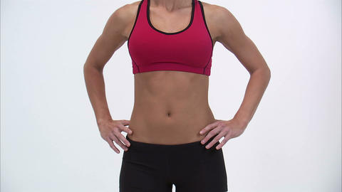 Front of a woman in workout clothes as she puts her hands on her hips Footage