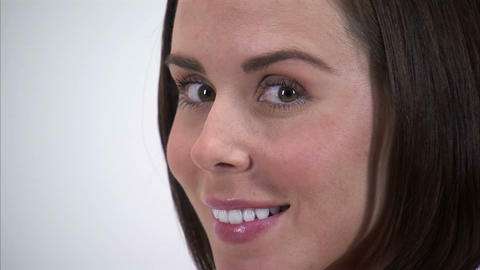 Close-up of a woman's face as she turns and smiles at the camera Footage