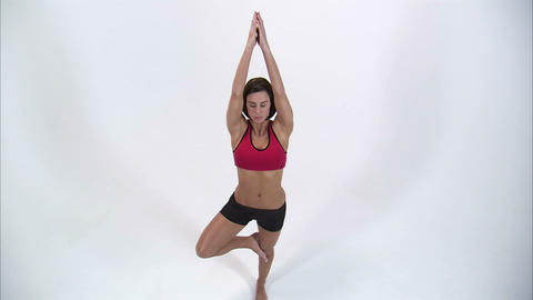 Jib shot of a woman doing a yoga pose on a white background Footage