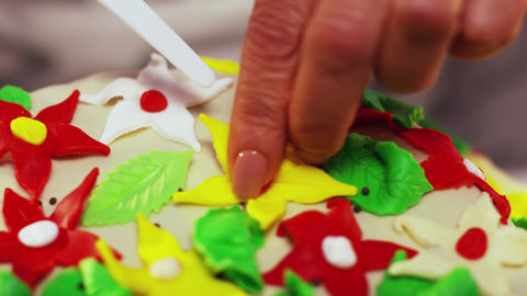 Cake decoration with small colorful star shaped flowers on curved white surface Footage