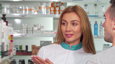 Friendly female pharmacist helping a customer at the drugstore Footage