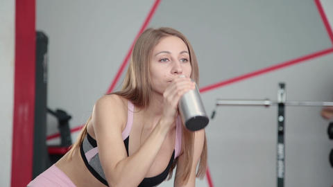 Beautiful athletic young girl resting after classes in the gym and drinking Footage