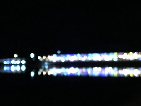 blurred bokeh photography of shopping buildings with reflection on lake Fotografía