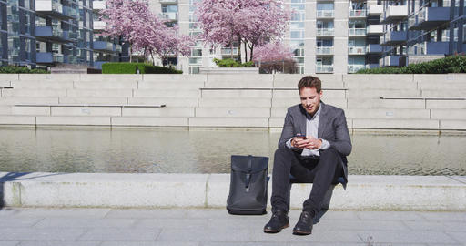 Man using phone - Smiling Business man With Backpack Using Smartphone In City Footage