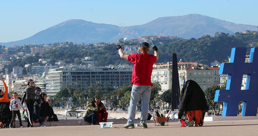 Street Artist Making Large Soap Bubbles With Beautiful Nice City Panorama In The GIF