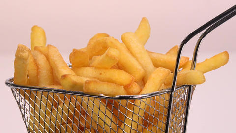 French fries in a small iron frying basket on turntable Live Action