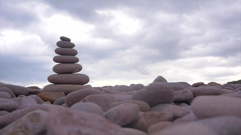 Stones pyramid on pebble beach, symbolizing zen, harmony, balance,motion Footage