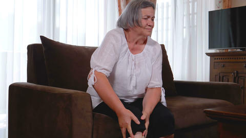 Elderly woman suffering from pain in knee at home Live Action