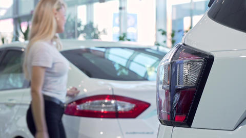 Woman choosing new car at the dealership, copy space Footage