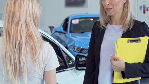 Female customer receiving car keys, shaking hands with saleswoman Live Action