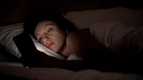 Young woman in bed with smartphone. Woman starring at cellphone device before Footage