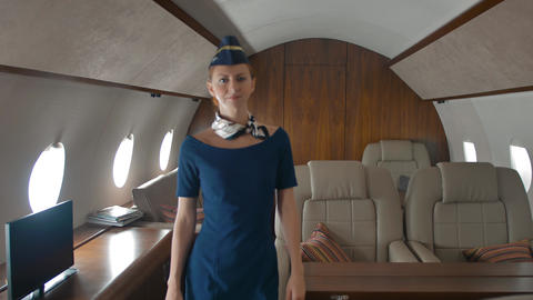 Beautiful smiling stewardess checking airplane's salon and walking to camera Footage