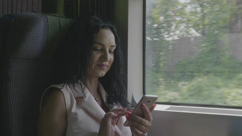 Stylish young woman commuting on train smiling while she browsing internet Footage