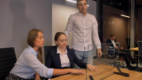 Few businesspeople, male and 2 women, work with modern future transparent glass Footage