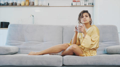 Young woman in a bathrobe sit well in the room on the couch. He drinks coffee Footage
