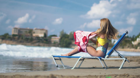 Young beautiful blondie lie down on the chaise longue near blue sea, remove red Footage