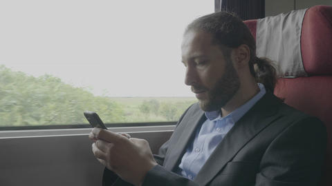 Young entrepreneur man commuter on train sitting next the window using Footage