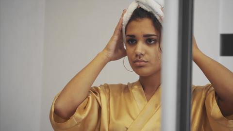 Close-up portrait of attractive Caucasian smiling woman brunette. Fixes hair Footage
