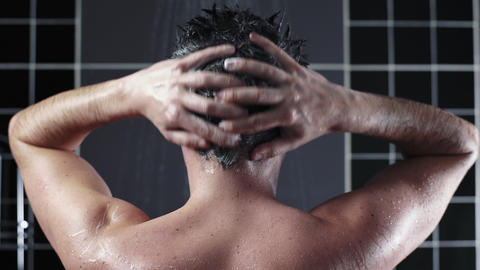Man washes his hair with shampoo in the shower, hair care, ceratin mask, rinse Live Action