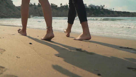 Legs of man and woman walking along the beach close up. Couple walks on sand Live Action