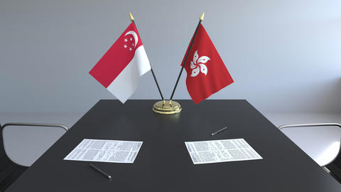 Flags of Singapore and Hong Kong and papers on the table. Negotiations and Live Action