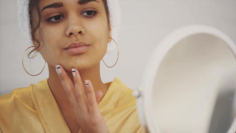 Quiet beauty. Portrait of a calm young lady standing in front of the mirror and Footage