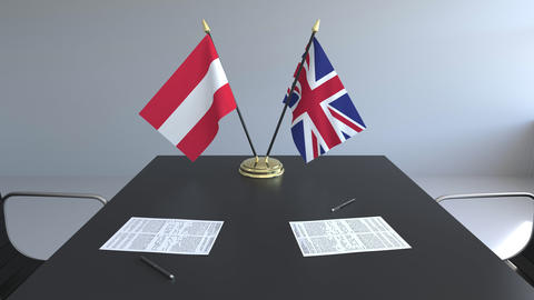 Flags of Austria and Great Britain and papers on the table. Negotiations and Live Action