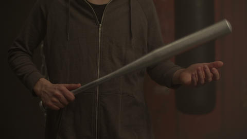 Midsection of violent hooligan holding baseball bat Live Action