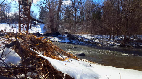 Snowy Bank River in Winter. Cold Water Flowing Under Walkway Bridge With Snow Footage
