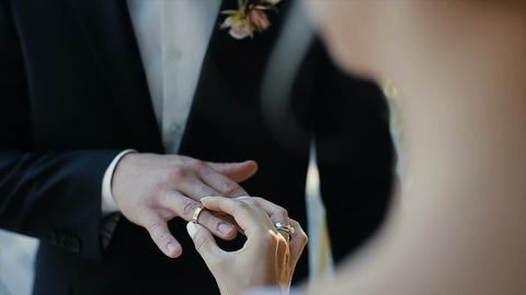 The bride puts the wedding ring on finger of the groom. marriage hands with ビデオ